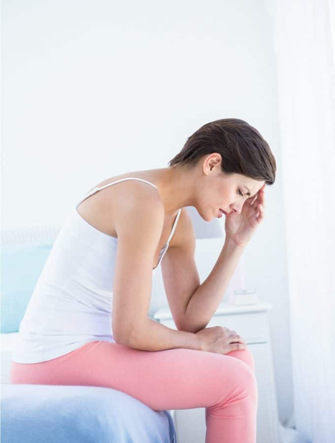 A woman with short dark hair sits on the edge of a bed with a blue bedspread in a white room. She's wearing a white tank top and pink pants, she's hunched over with her elbows on her thighs and her left hand holding her head. Her face looks distressed and in pain.
