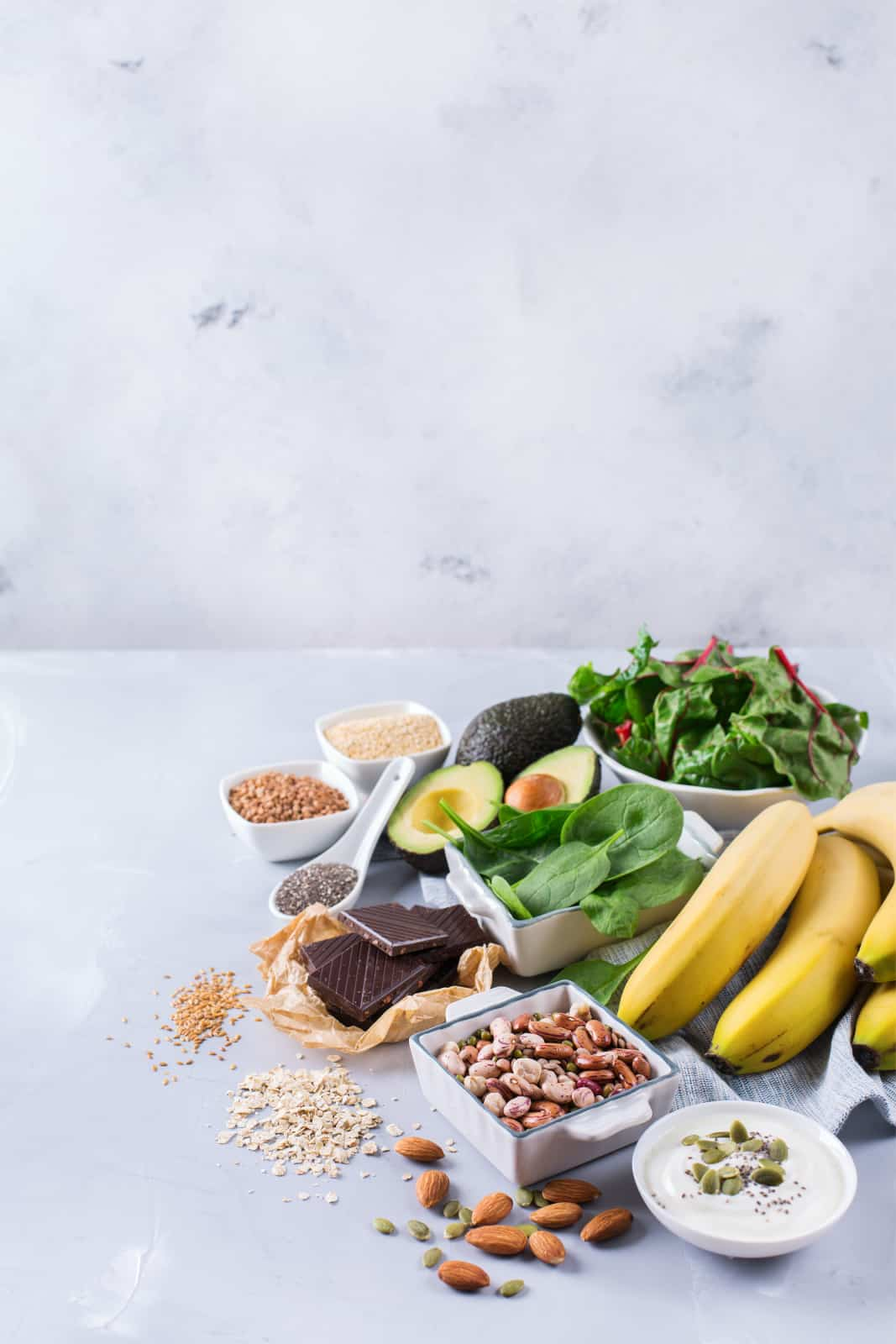 A white marble backdrop and countertop is piled with magnesium rich foods: spinach, bananas, avocado, almonds, dark chocolate, seeds, chia seeds, and Swiss chard.