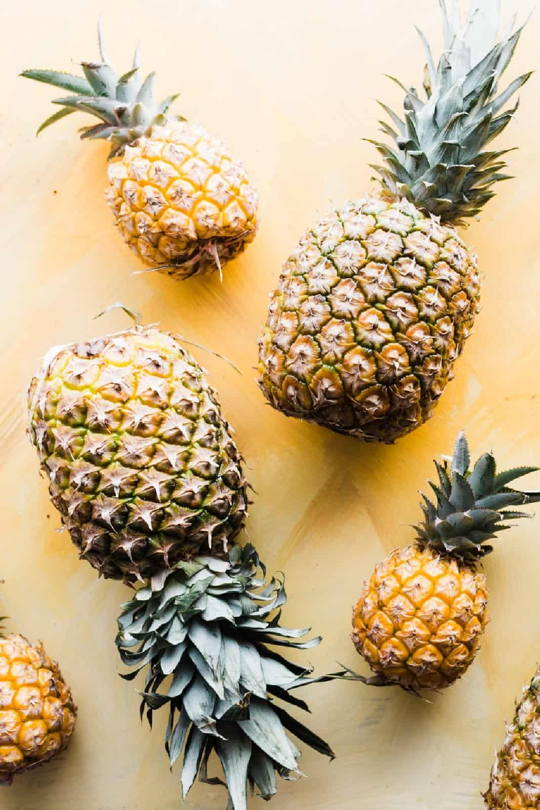 Overhead shot of various pineapples on a yellow background.