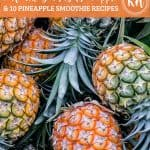 "Overhead shot of pineapples piled on top of each other with an orange banner. The first line of text on the banner reads, ""10 Health Benefits of Pineapple"" in script. The second line reads, ""& 10 Pineapple Smoothie Recipes,"" in a bold caps font. To the right is a white dotted circle with KH in the middle."
