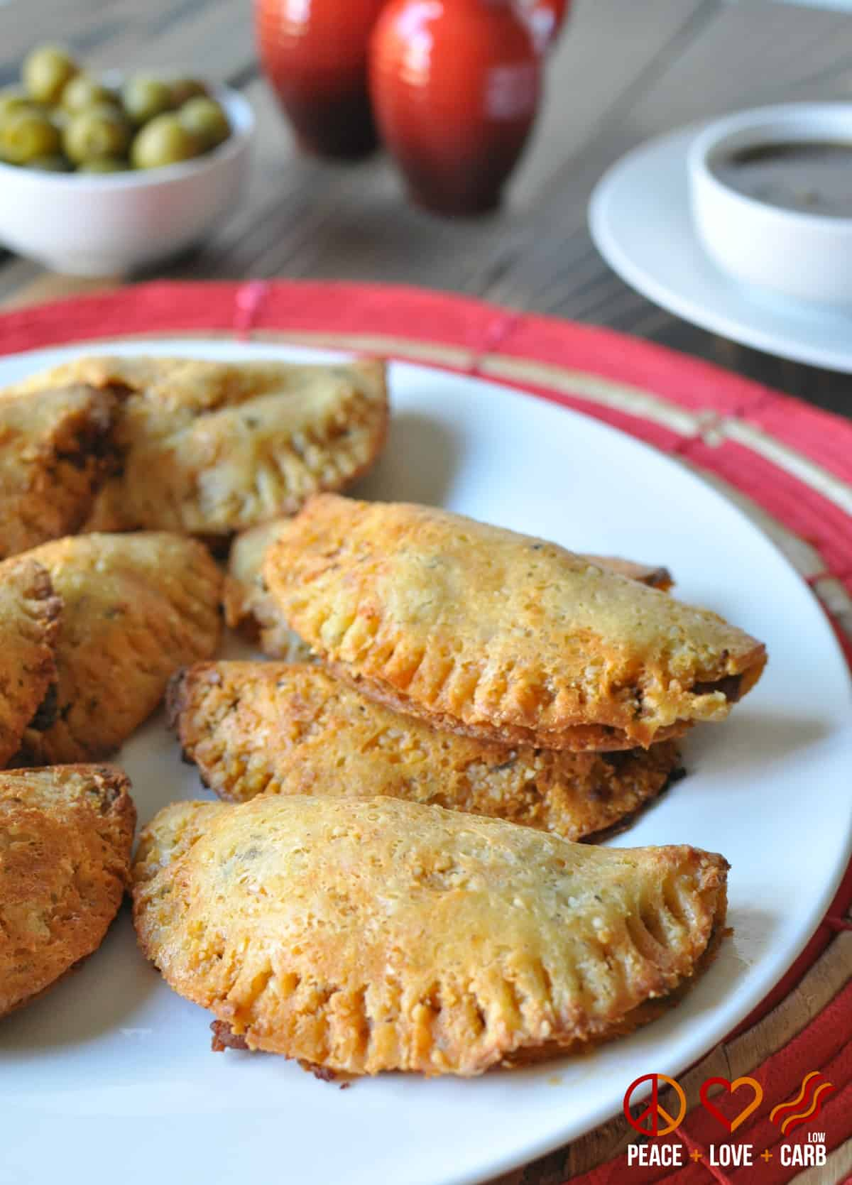 Beef and chorizo empanadas are stacked on a white plate on a gray wooden table with a red table cloth. In the background sits a white bowl of green olives, red salt and pepper shakers, and a white bowl of dipping sauce on a white charger.