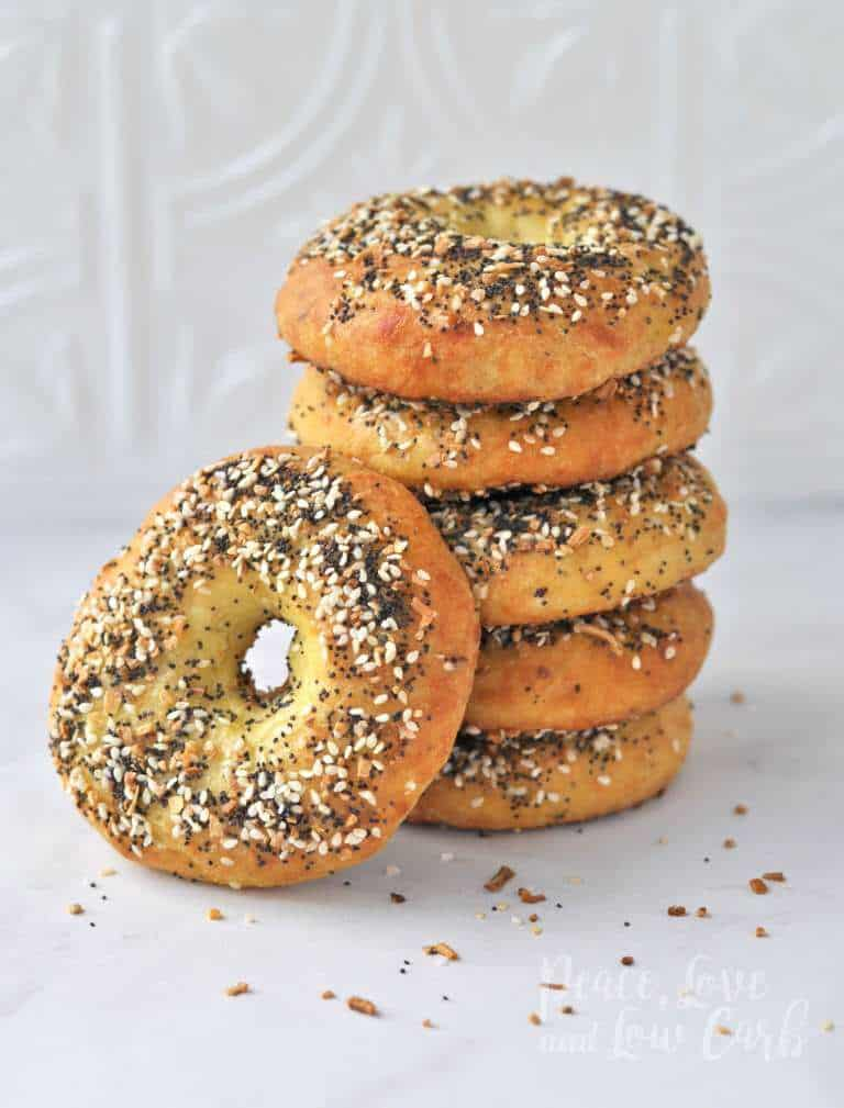 5 low carb everything bagels stacked with an additional bagel on the left side of the pile, leaning on the stack. A bit of seasons are sprinkled on the marble countertop, with a white tile patterned background.