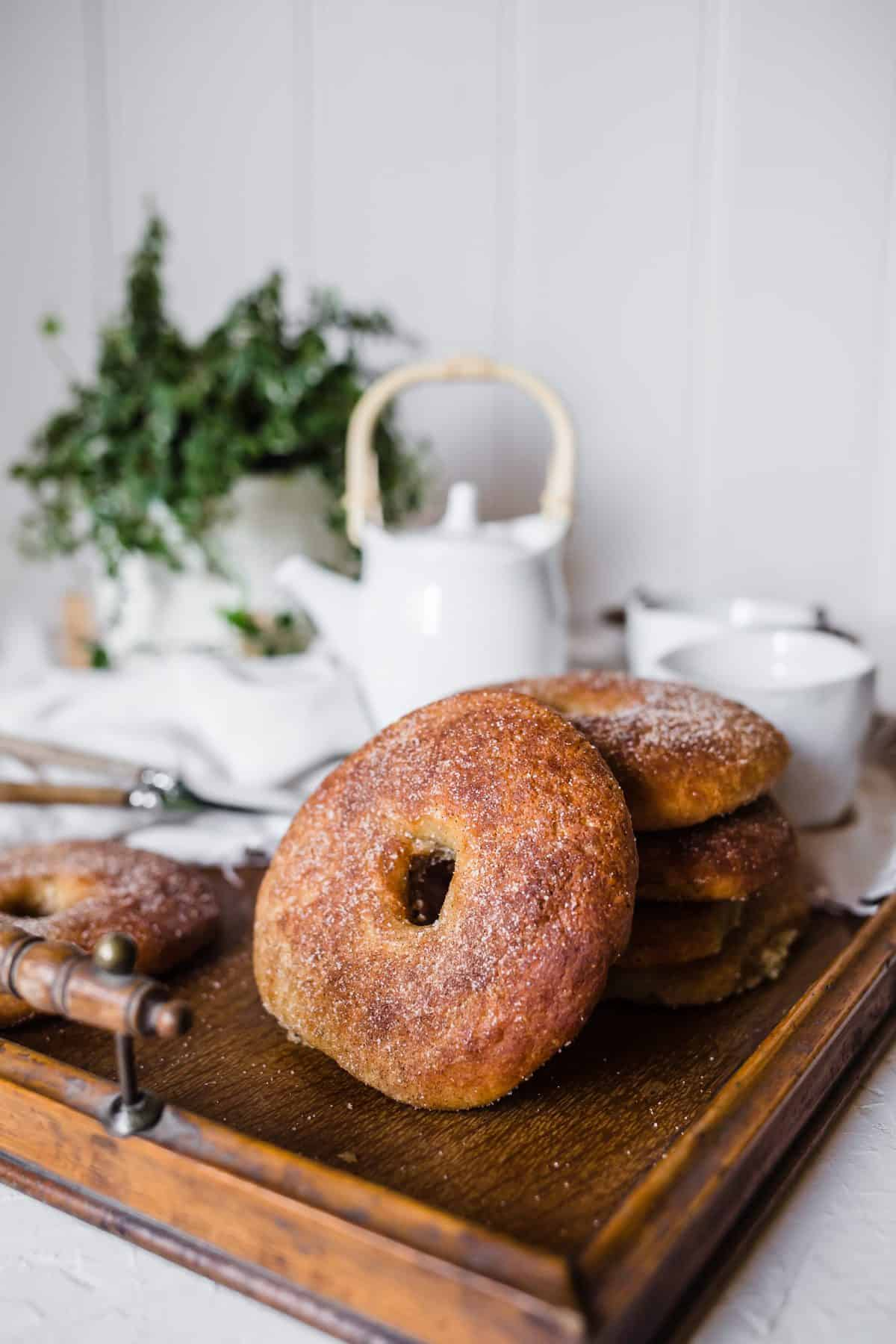 Cinnamon sugar(free) bagels are stacked on a wooden tray with a white tea set and a potted plant in the background.