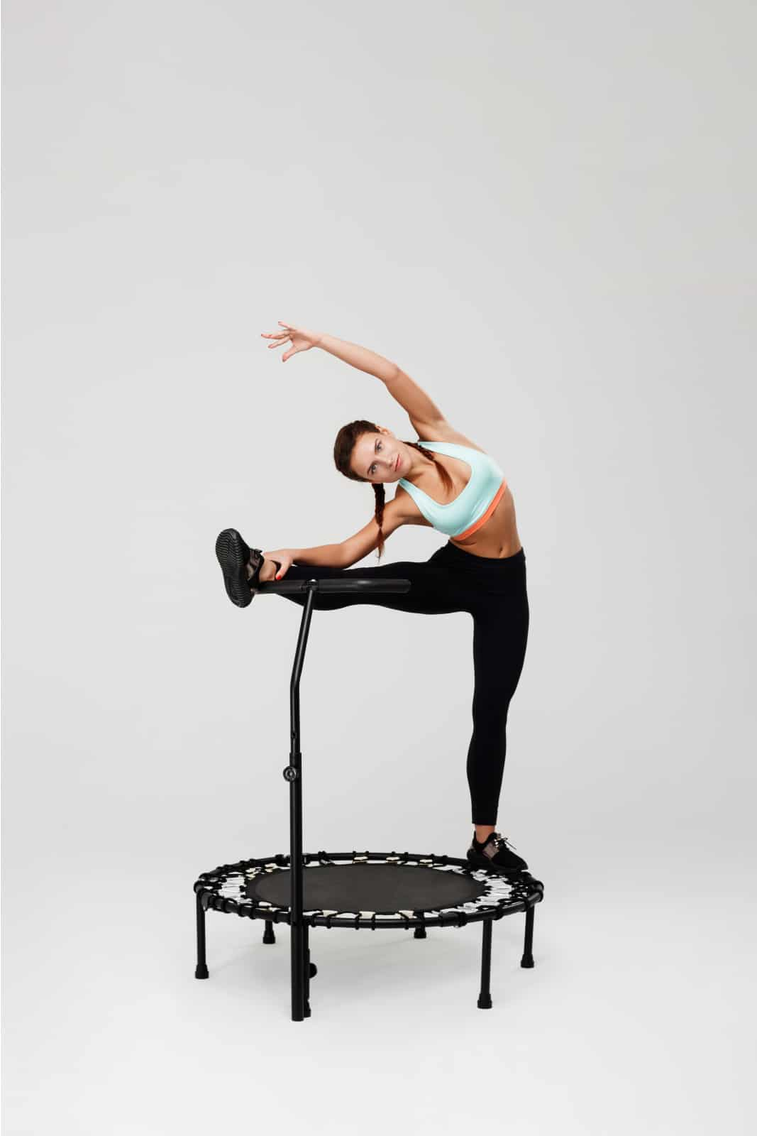 A woman wearing braided pigtails and a light blue and orange sports bra with black shoes and leggings stretches with her leg up and opposing arm arched up over her head on a black rebounding trampoline.