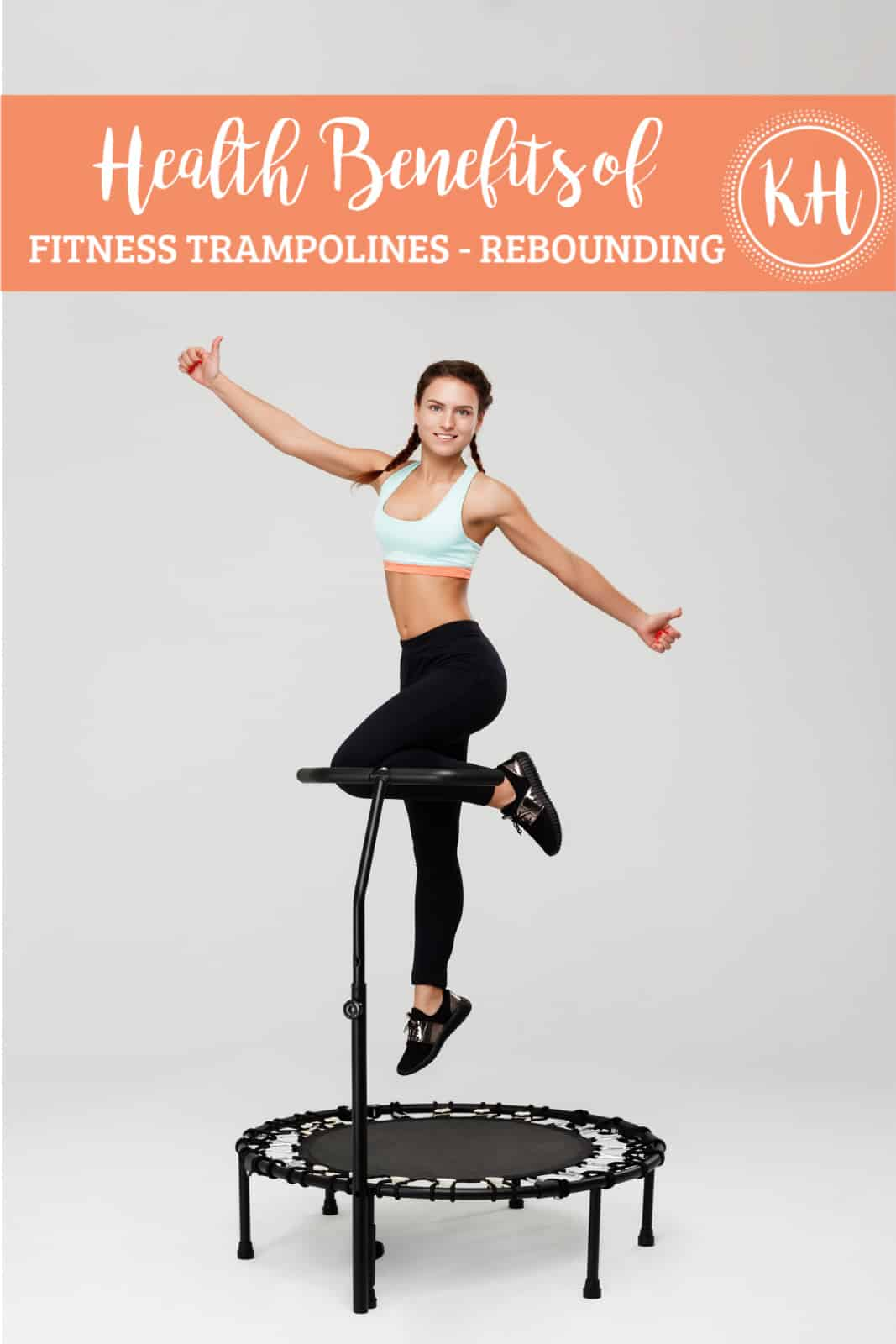 "A woman wearing braided pigtails and a light blue and orange sports bra with black shoes and leggings jumps on a black rebounding trampoline. Above the woman is an orange band with ""Health Benefits of"" written in script and a second line of bold caps text ""FITNESS TRAMPOLINES - REBOUNDING"". To the right on the banner is the KH logo."