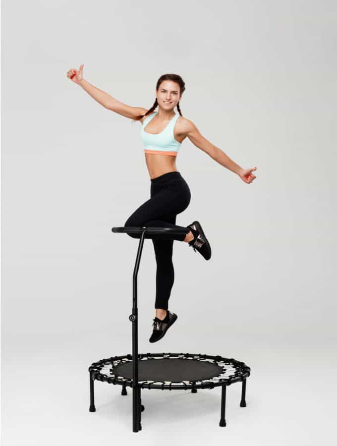 A woman wearing braided pigtails and a light blue and orange sports bra with black shoes and leggings jumps on a black rebounding trampoline.