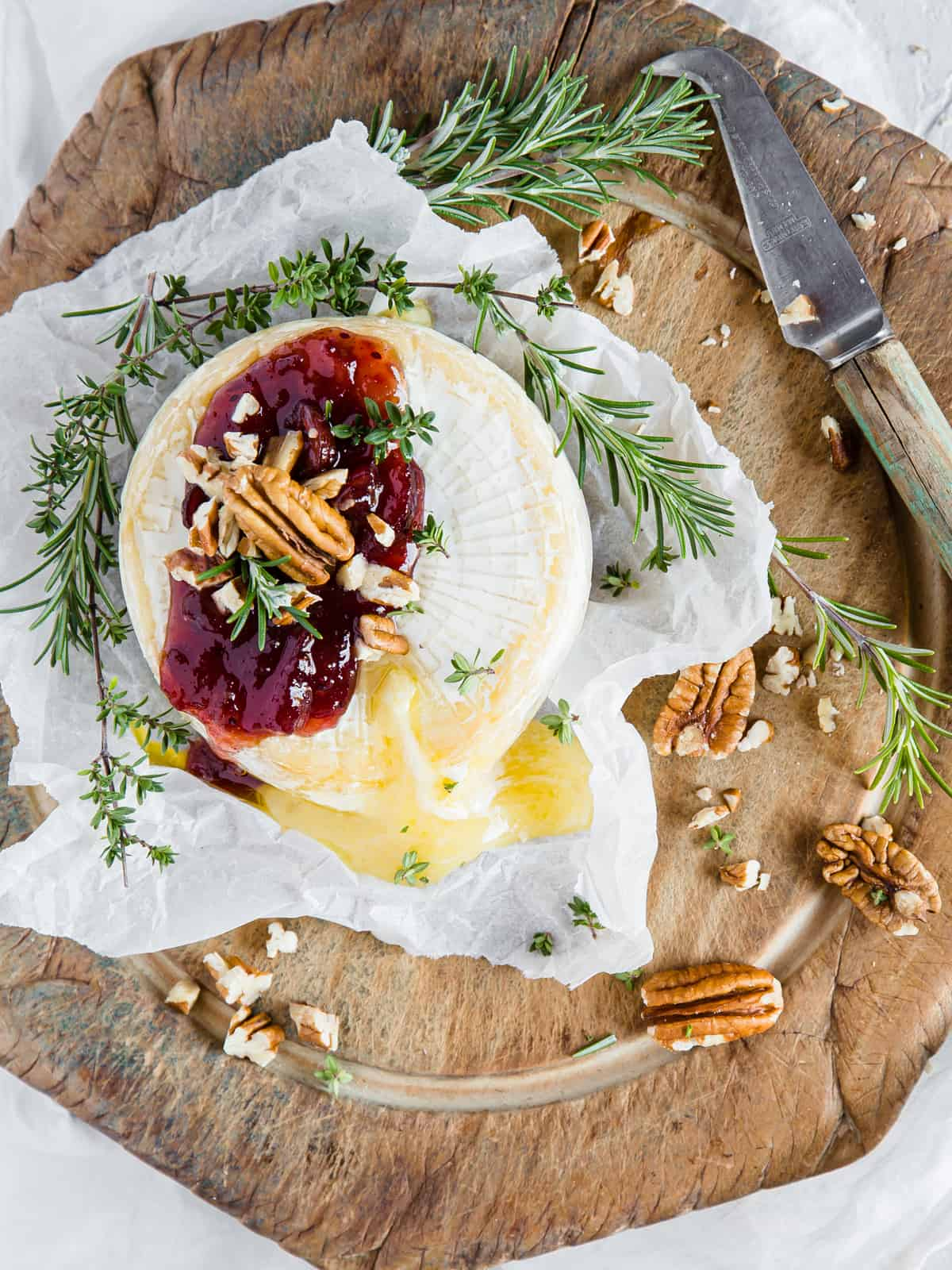 baked brie with cranberry sauce and pecans, garnished with fresh herbs and served with crackers