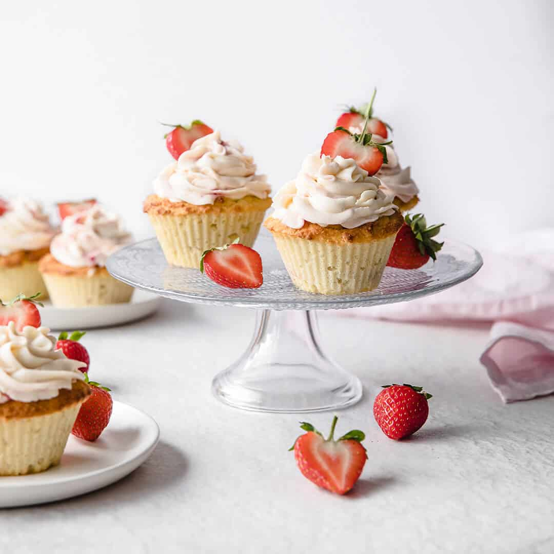 lemon cupcakes frosted with strawberry cream cheese frosting, served on a cake stand, with fresh strawberries