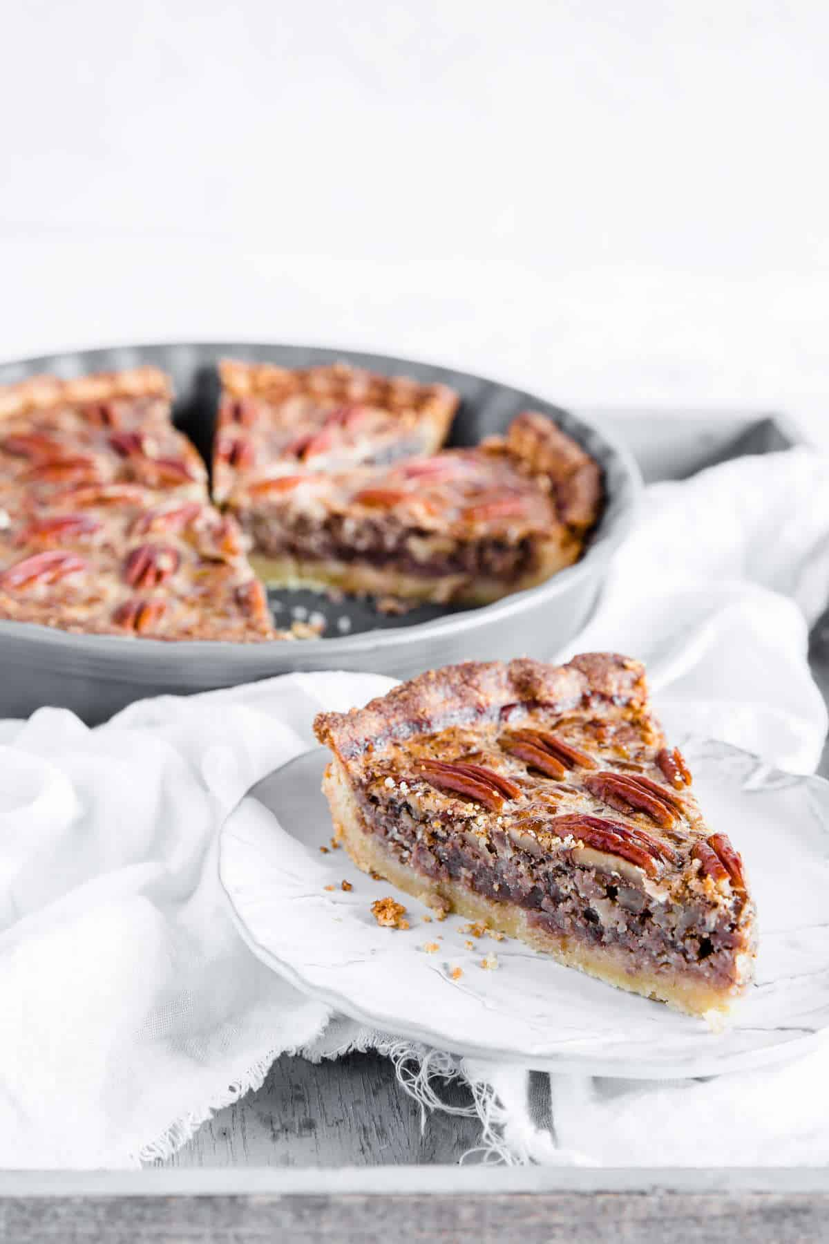 slice of low carb pecan pie with the whole pie in the background