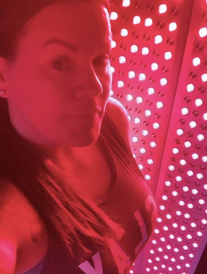 Woman standing in front of a Joovv Elite Red Light Therapy Unit