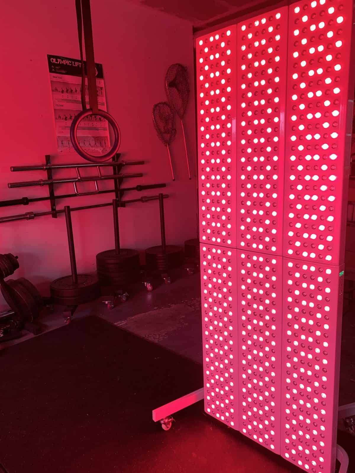 Joovv Elite Red light Therapy Unit , lit up in a garage gym