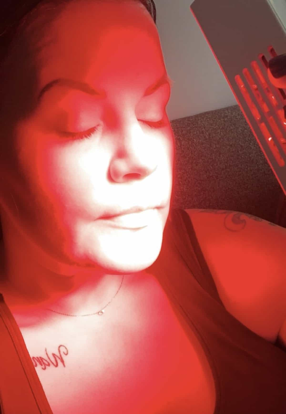 Women using a handheld red light therapy unit on her face