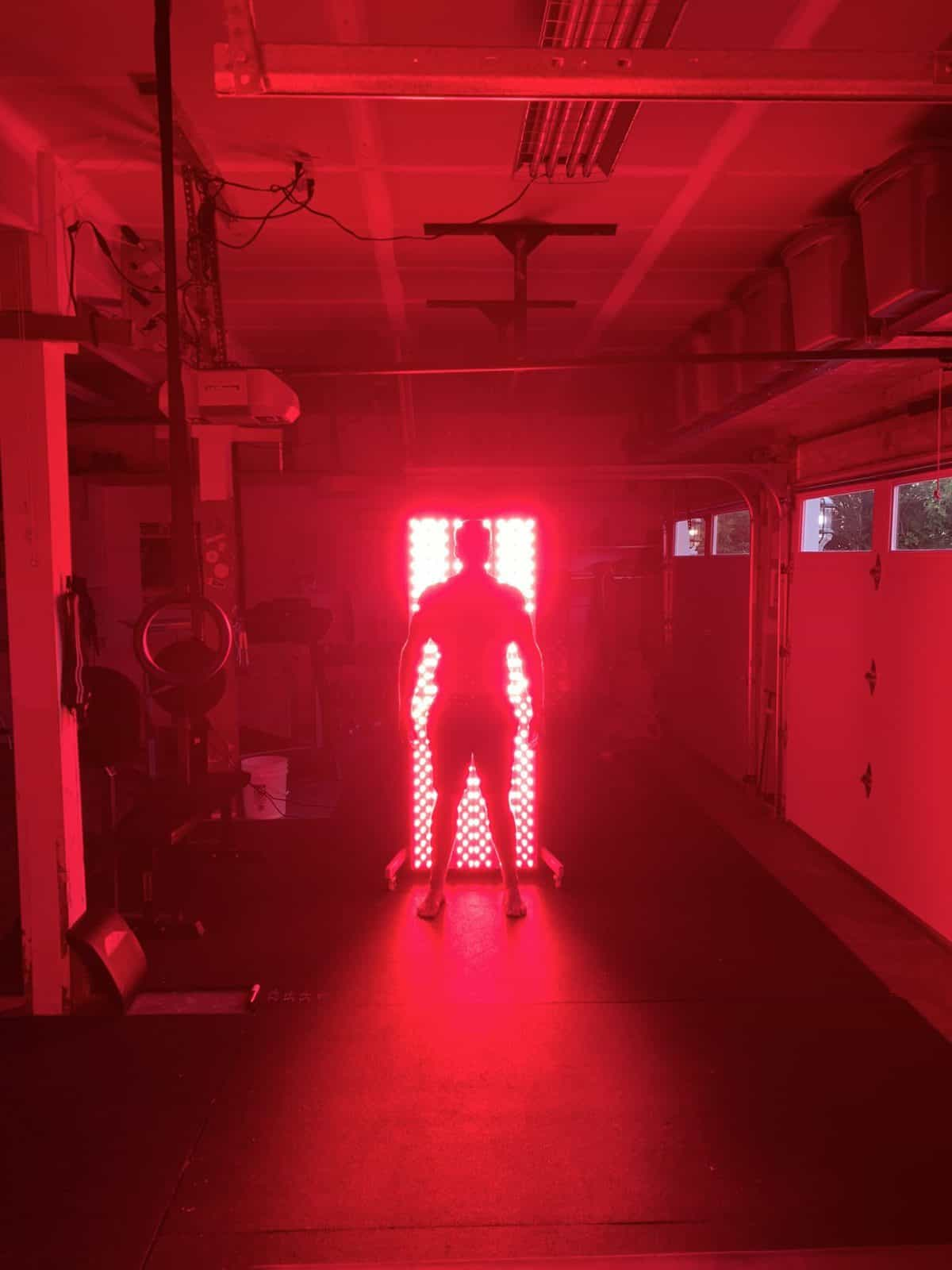 Silhouette of a man in front of a red light therapy unit