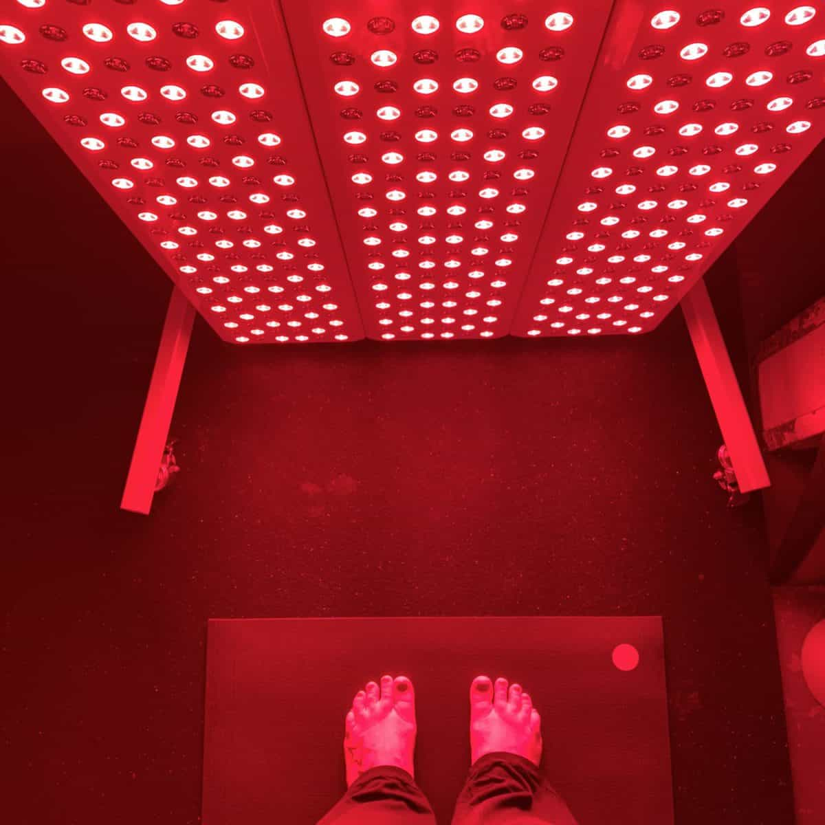 Women standing on a yoga mat in front of a red light therapy unit