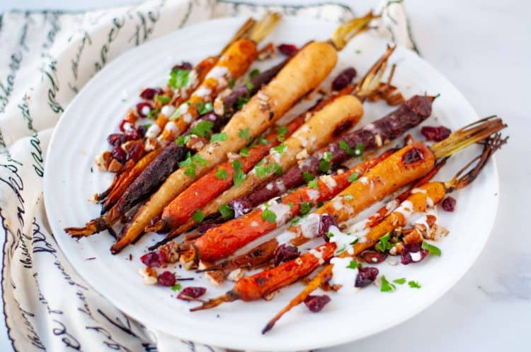 Roasted Rainbow Carrots with Cranberries and Pecans, drizzled with a orange coconut yogurt, sprinkled with fresh herbs, on a white round plate with a fabric napkin to the left. The napkin has decorative script writing.