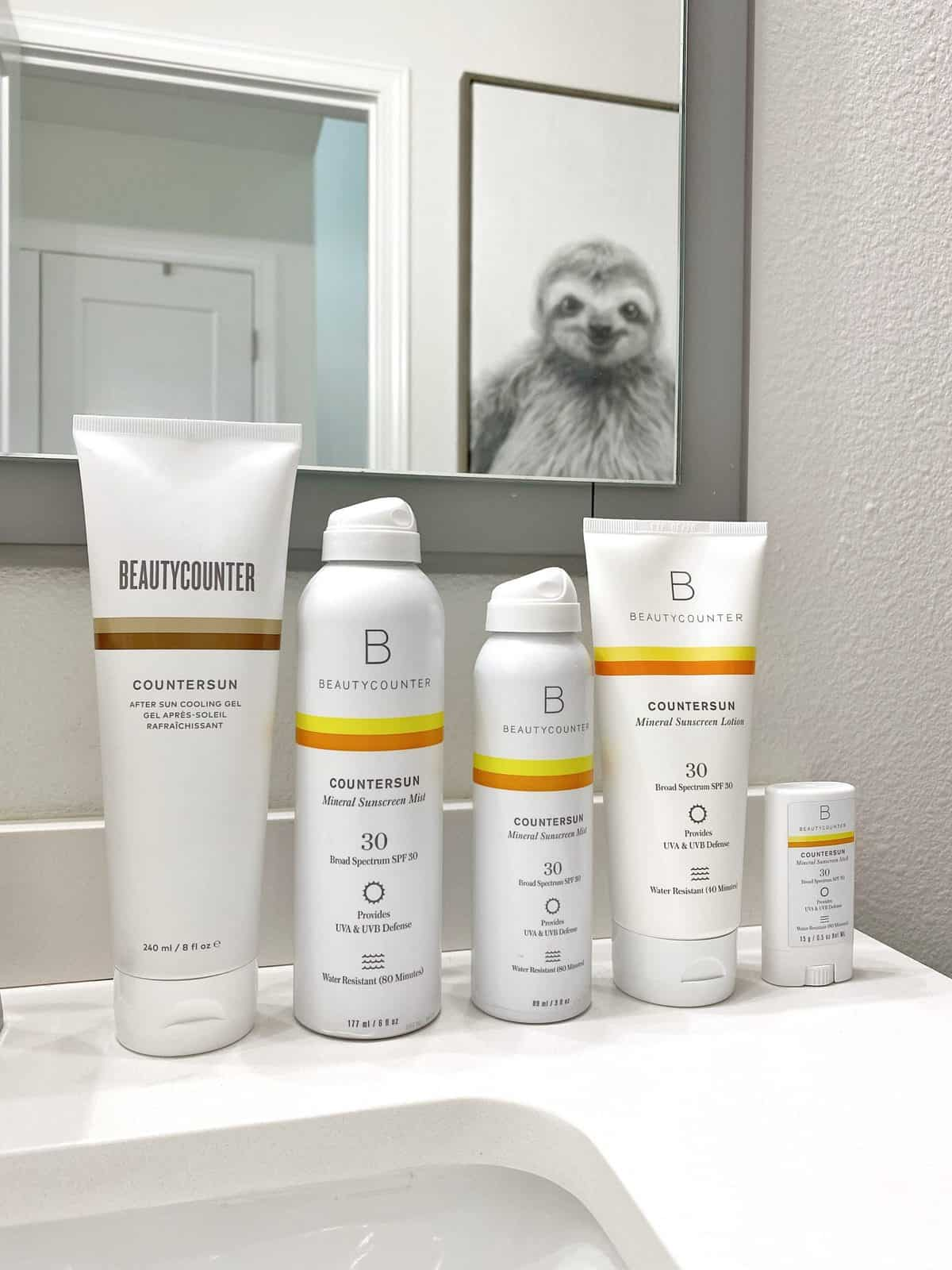Beautycounter sunscreen lined up on a bathroom vanity: Countersun After Sun Cooling Gel, Countersun Mineral Sunscreen Mist SPF 30, Countersun Mineral Sunscreen Lotion SPF 30, and Countersun Mineral Sunscreen Stick SPF 30. Above the bathroom vanity is a mirror that reflects back a framed photo of a sloth.