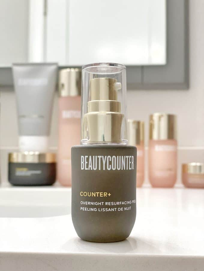 The Counter+ Overnight Resurfacing Peel sits on a white bathroom vanity. In the background, the Countertime collection sits below a mirror, along with the Countercountrol Exfoliating Mask.