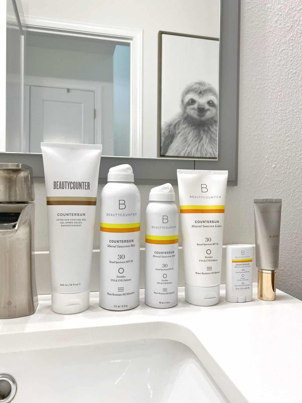 Beautycounter sunscreen lined up on a bathroom vanity: Countersun After Sun Cooling Gel, Countersun Mineral Sunscreen Mist SPF 30, Countersun Mineral Sunscreen Lotion SPF 30, Countersun Mineral Sunscreen Stick SPF 30, and Dew Skin. Above the bathroom vanity is a mirror that reflects back a framed photo of a sloth.