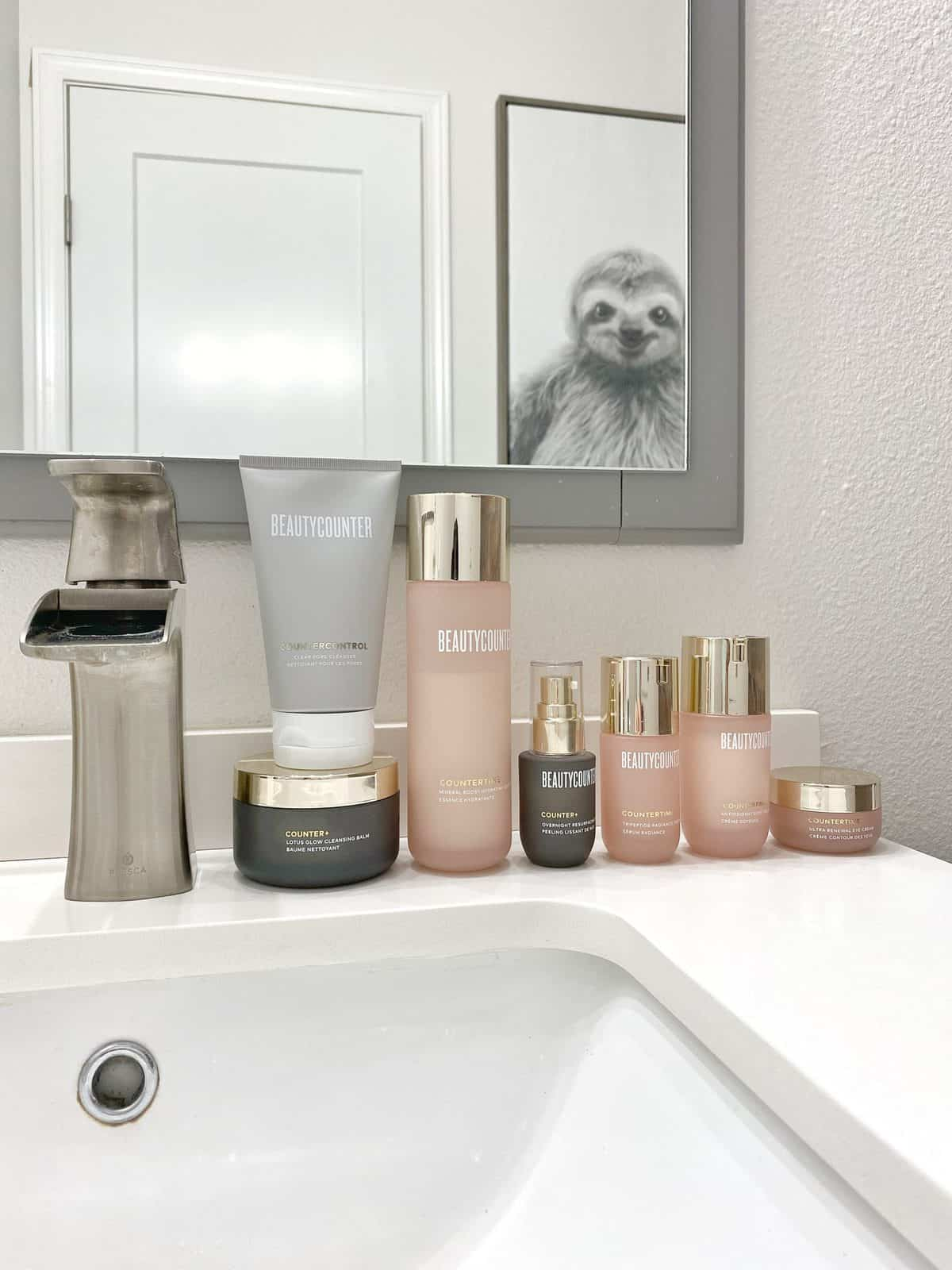 My skincare lineup sits on a white bathroom vanity, including the Countercountrol Exfoliating Mask, the Counter+ Lotus Glow Cleansing Balm, the Countertime collection, and the Counter+ Overnight Resurfacing Peel. Above the skincare is a bathroom mirror, which reflects a sloth portrait on the opposing wall.
