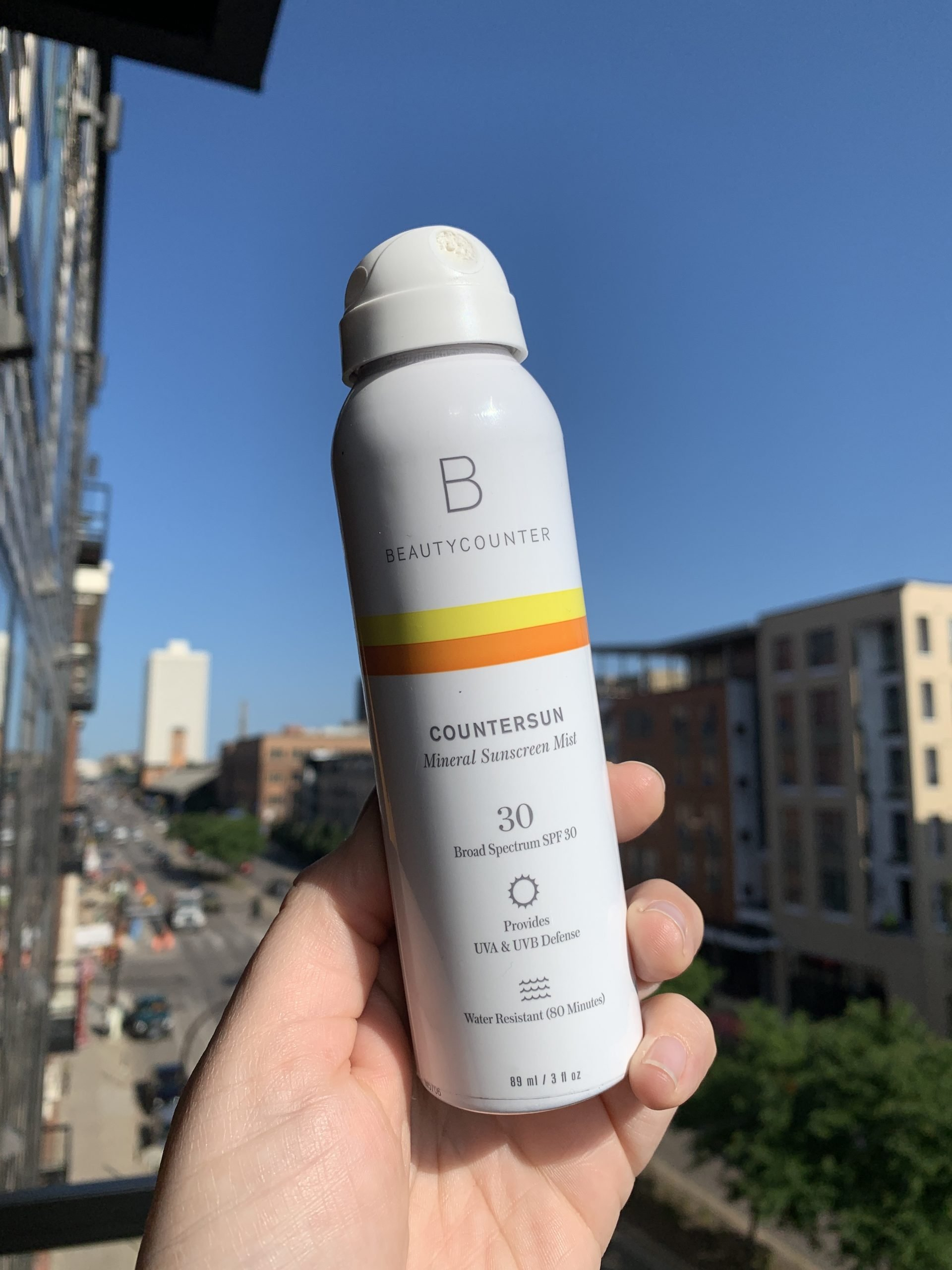 A hand holding a bottle of Countersun Mineral Sunscreen Spray in front of a city landscape with a beautiful blue sky in the background.