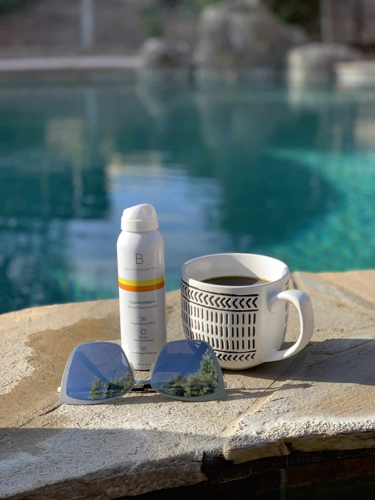 A bottle of Countersun Mineral Sunscreen Spray sits on a stone wall next to a cup of coffee and a pair of upside down reflective silver sunglasses. In the background is a crystal clear blue green pool.