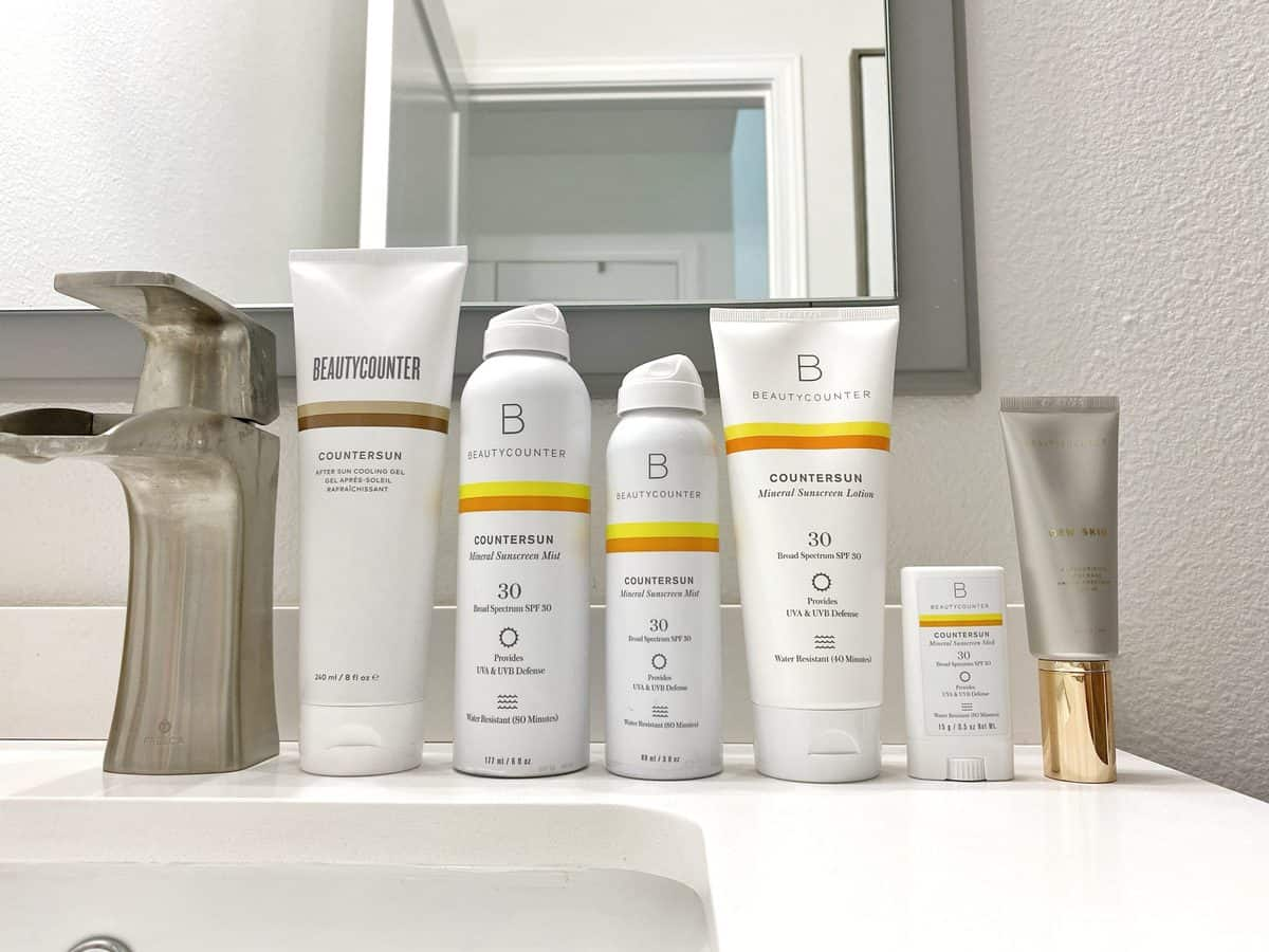 A wide shot of Beautycounter sunscreen lined up on a bathroom vanity: Countersun After Sun Cooling Gel, Countersun Mineral Sunscreen Mist SPF 30, Countersun Mineral Sunscreen Lotion SPF 30, Countersun Mineral Sunscreen Stick SPF 30, and Dew Skin.