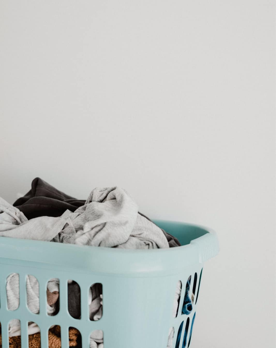 A pile of laundry in a light teal laundry basket sits against a white wall.