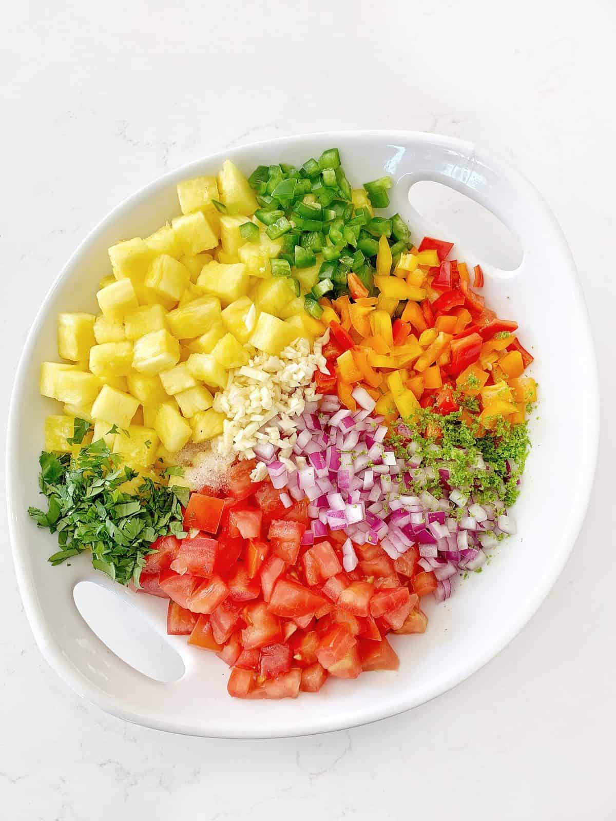 Overhead shots of fresh fruits and vegetables for Pineapple Salsa in a white bowl