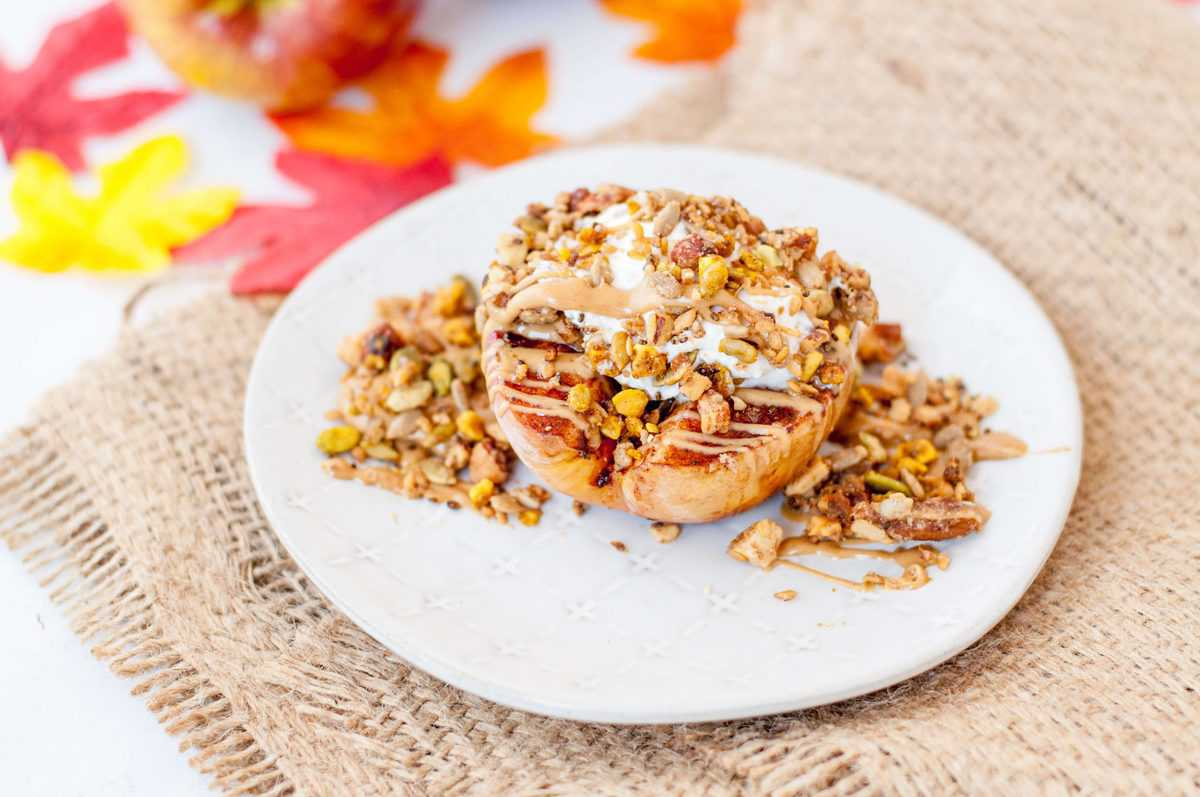 Baked Apple topped with granola, peanut butter, and whipped cream, surrounded by fall decorations