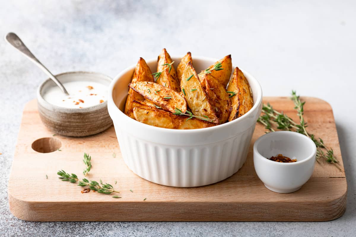 wood cutting board with a bowl of crispy potatoes, serves with ketchup and ranch