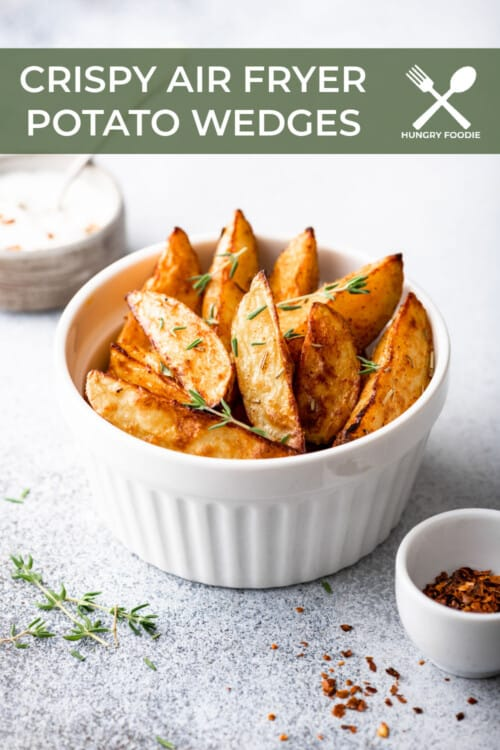 white bowl filled with crispy potato wedges, garnished with fresh thyme