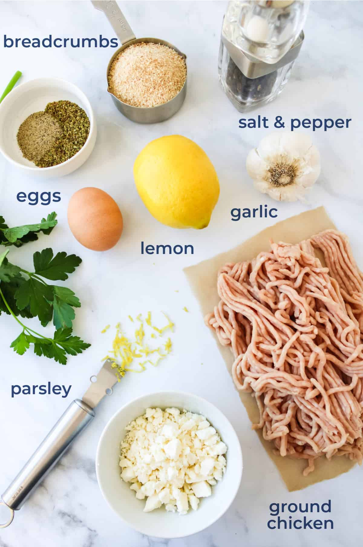 Ingredients laid out for greek chicken meatballs - chicken, feta, egg, lemon, herbs, breadcrumbs