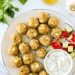 white plate with greek chicken meatballs, tomato salad and tzatziki sauce