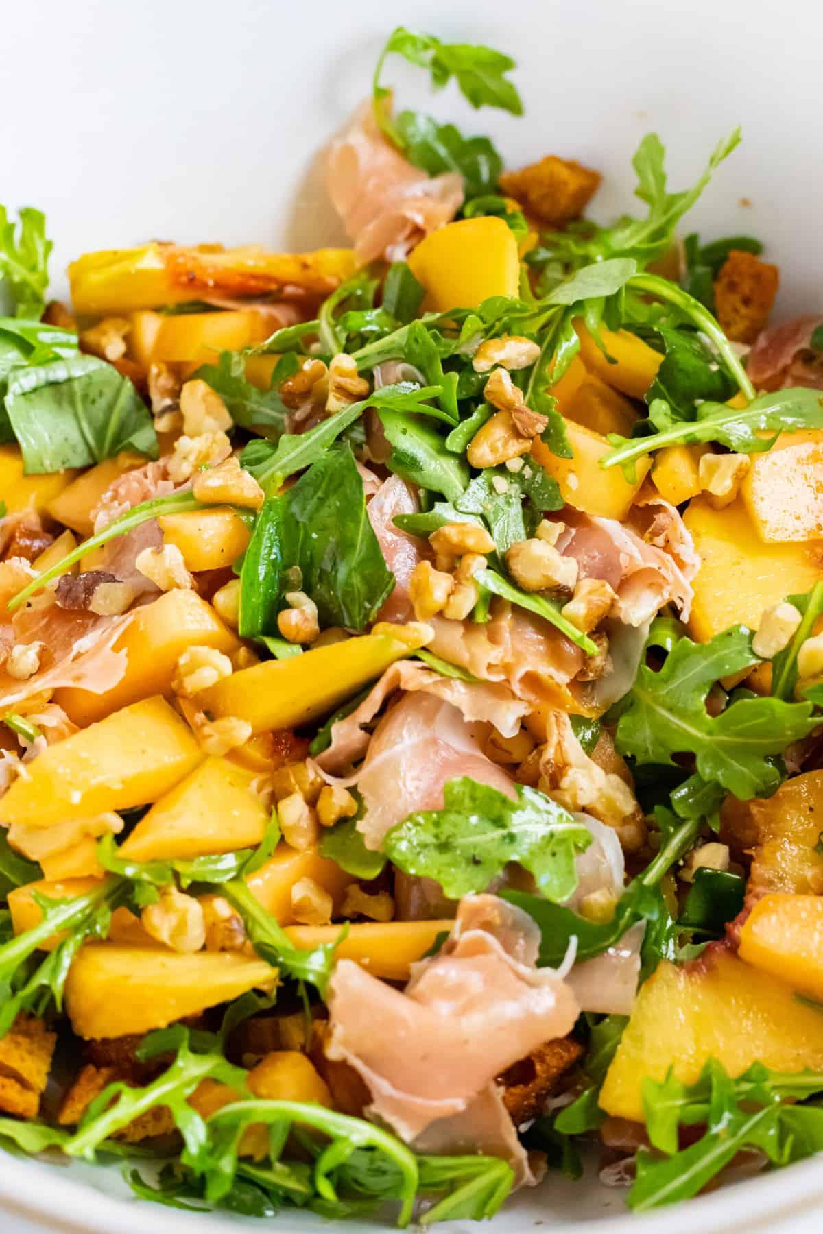 a fresh summer salad of prosciutto, peaches, melon, walnuts, croutons, feta, and arugula