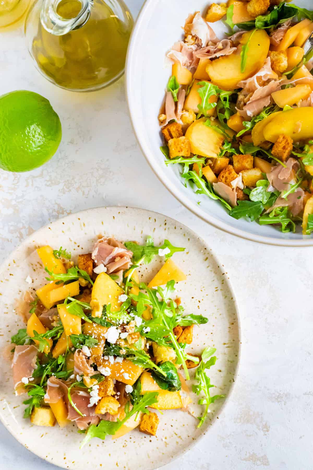 a white plate piled high with a fresh summer salad of prosciutto, peaches, melon, walnuts, and arugula