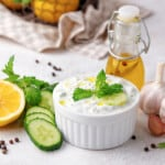 a white ramekin with greek cucumber sauce, surrounded by fresh herbs, lemons, garlic, and cucumbers