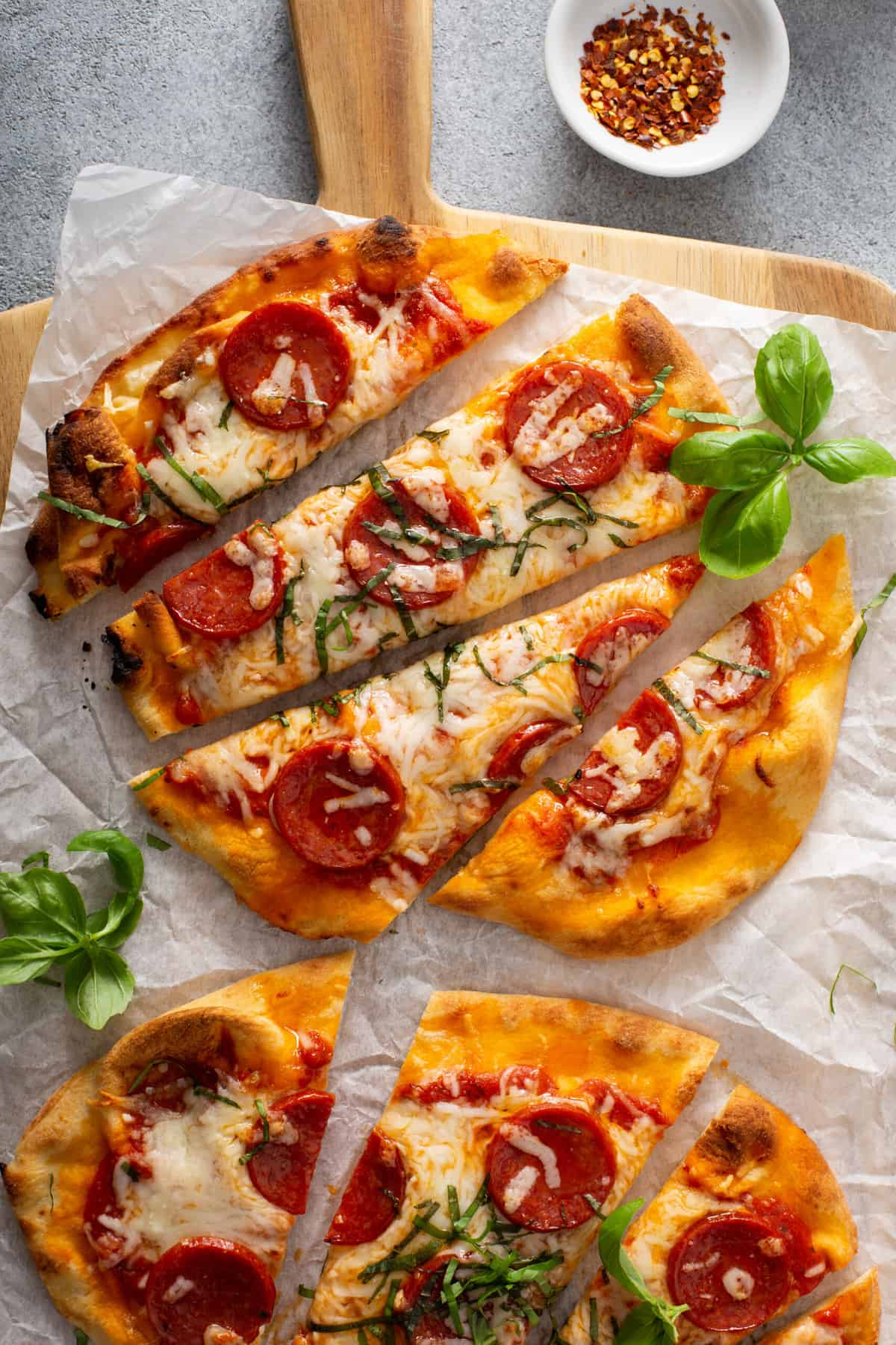 flatbread pizzas topped with pepperoni, cheese, and basil, on parchment paper, on a wood cutting board