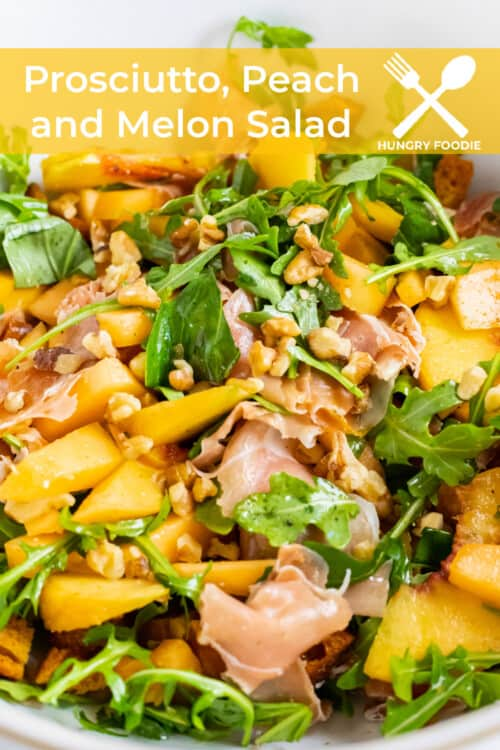a fresh summer salad of prosciutto, peaches, melon, walnuts, croutons, feta, and arugula on a white plate
