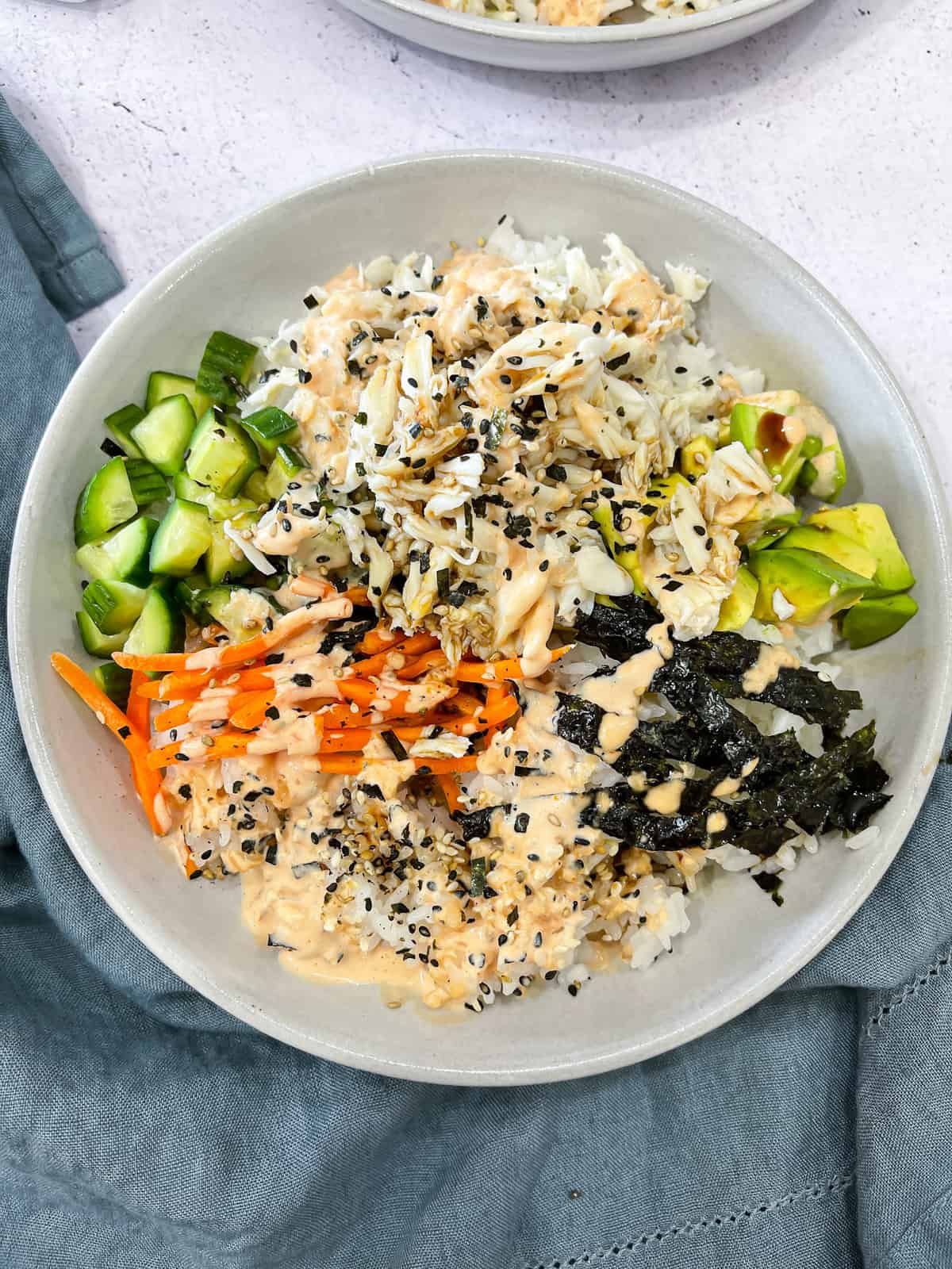 Ingredients for a california sushi roll all piled in a bowl - crab, rice, carrots, avocado, cucumber