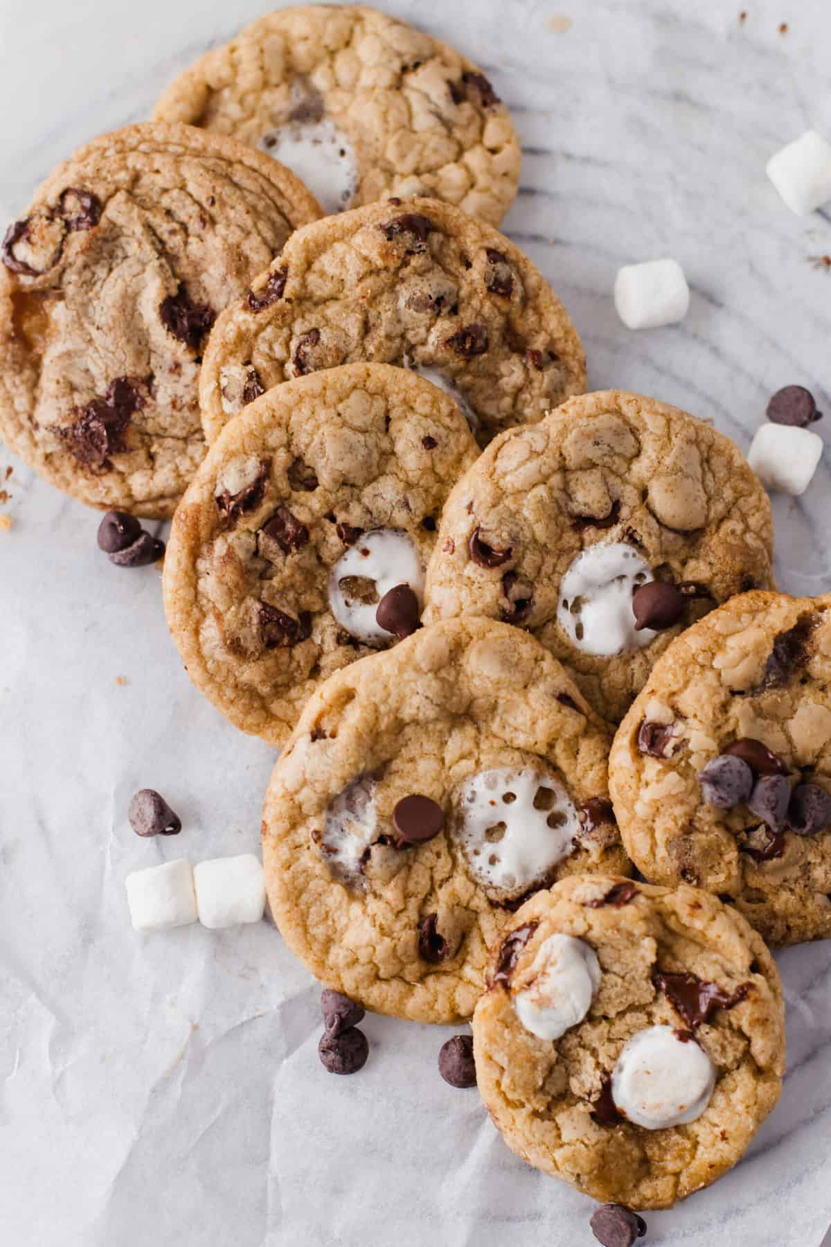 a pile of chocolate chip cookies with mini marshmallows and chocolate chips around it