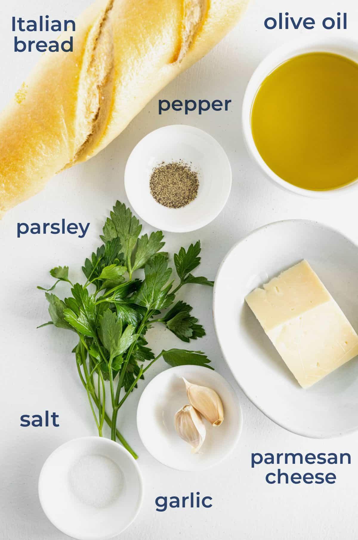 Ingredients for homemade croutons - bread, parmesan cheese, parsley, garlic, olive oil, seasonings