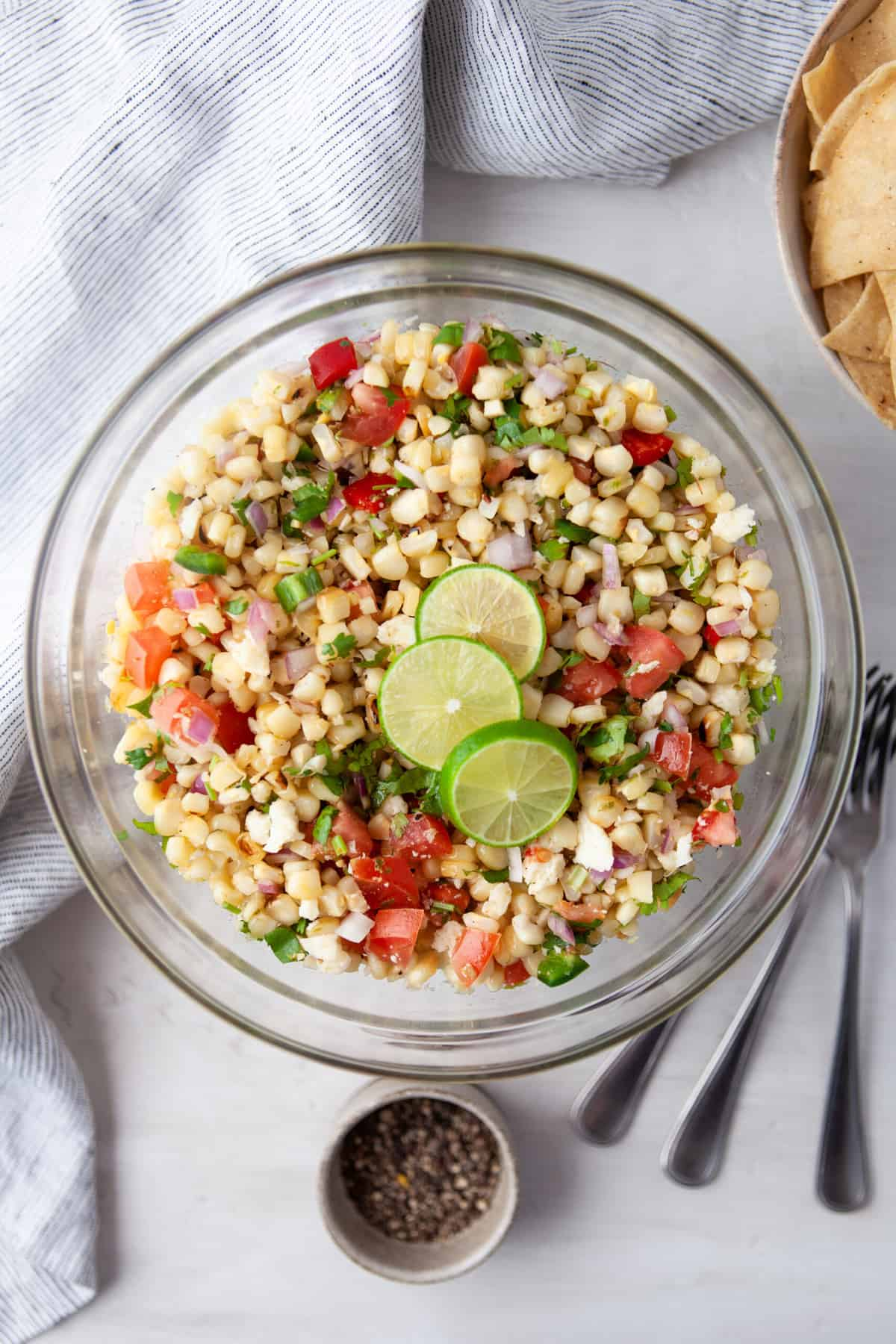 clear mixing bowl filled with grilled corn salsa, served with chips, guacamole and limes