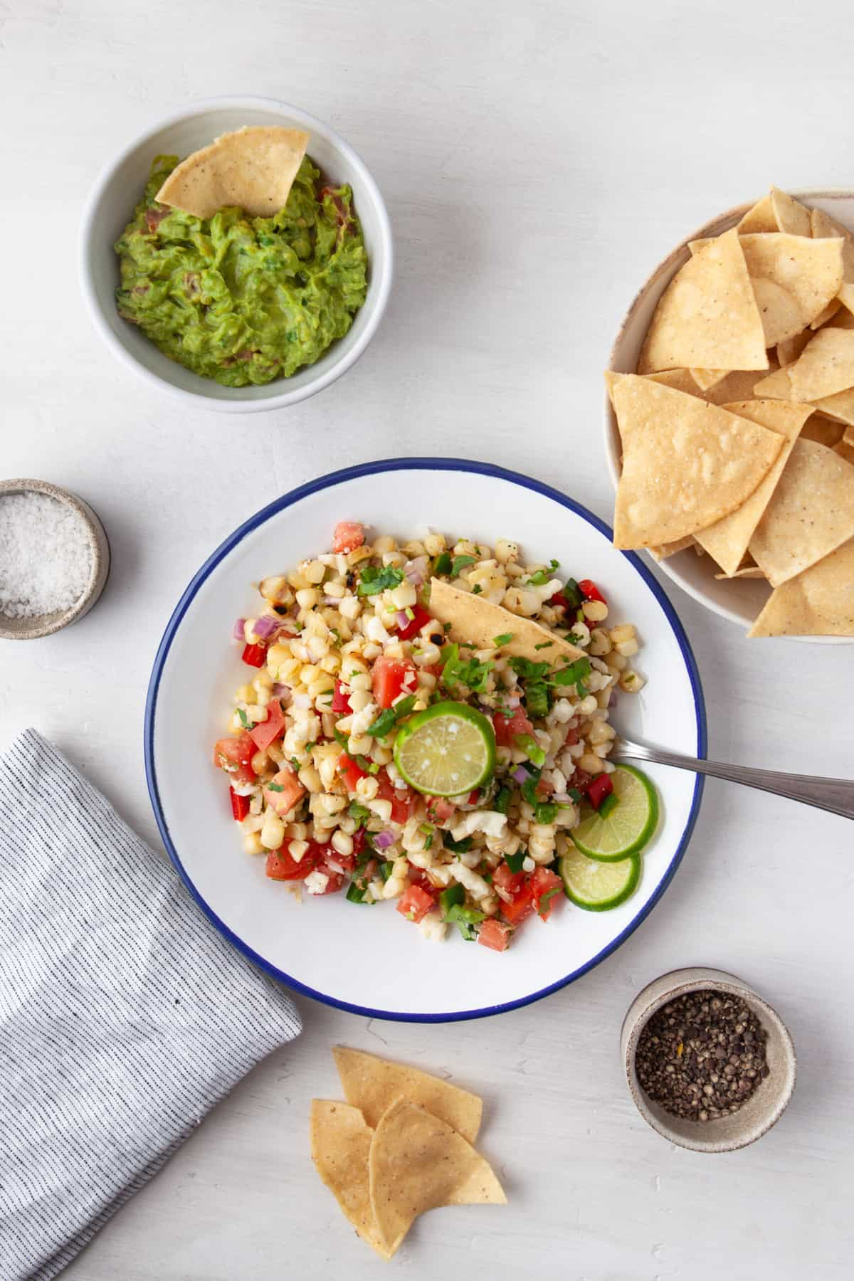 white bowl filled with grilled corn salsa, served with chips, guacamole and limes