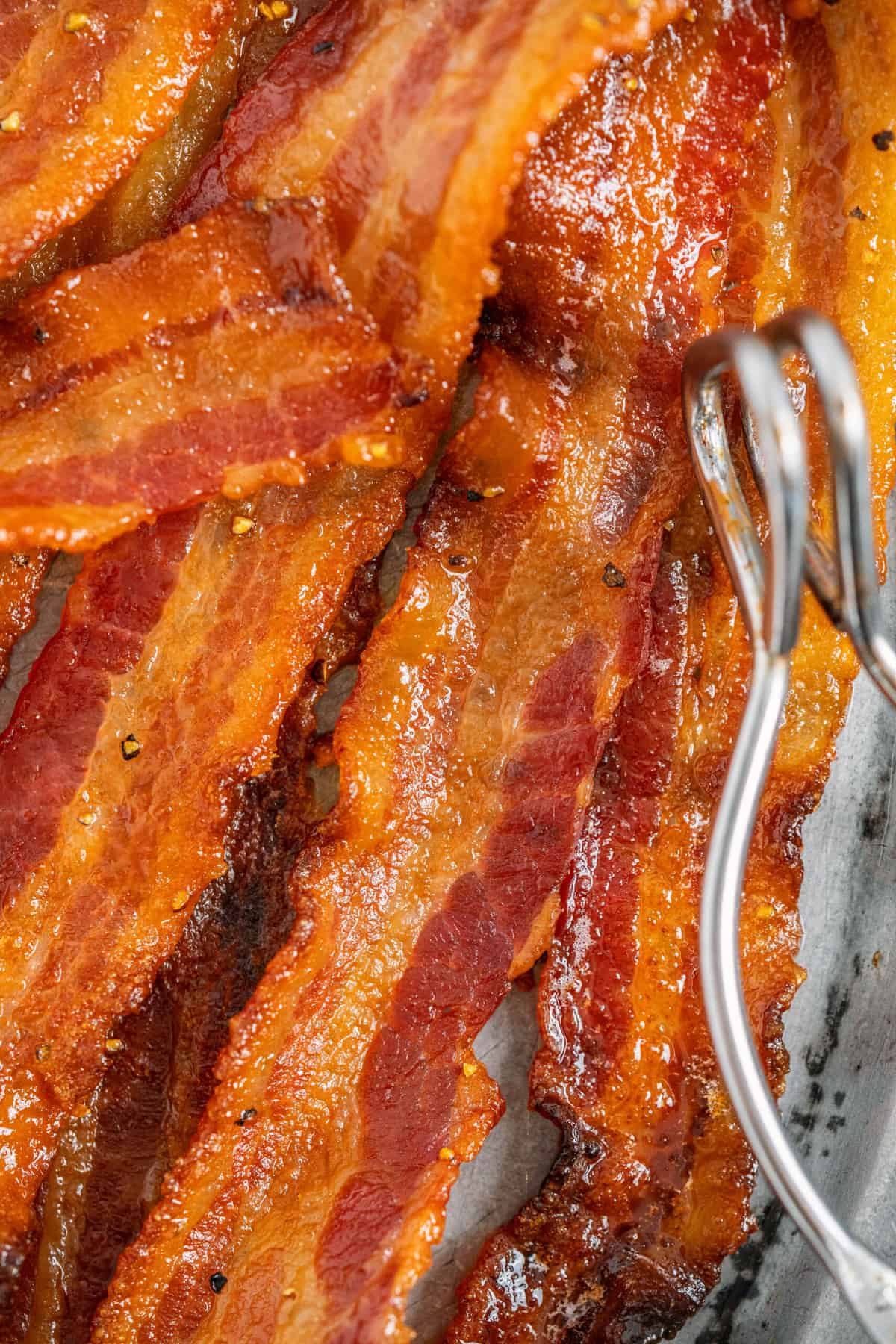 candied bacon lined on a bacon sheet  with tongs