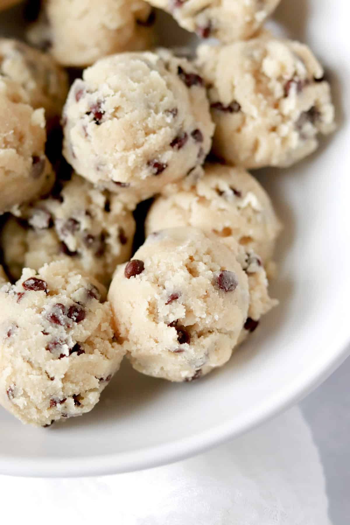 a white bowl full of chocolate chip cookie dough bites