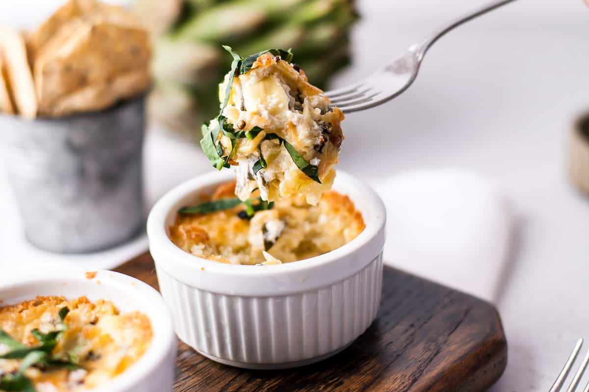 a white ramekin full of spinach and artichoke dip with a fork pulling a cheesy bite out of it