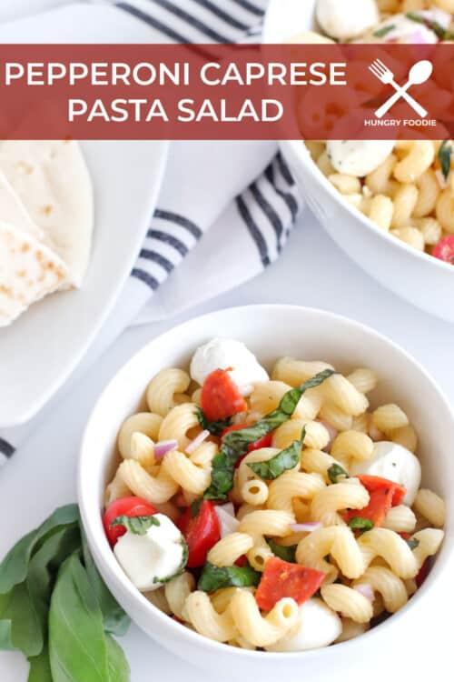 white bowl with pasta salad made of cavatappi, pepperoni, basil, tomatoes, and fresh mozzarella