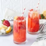 Tall glasses with a strawberry lemonade cocktail in them. Red and white striped straw, garnished with strawberries and lemons