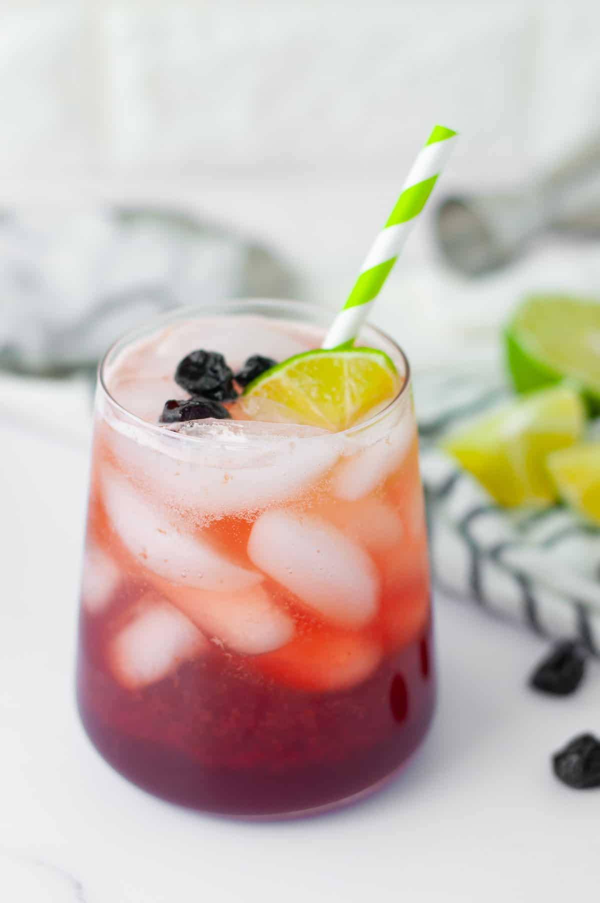refreshing summer cocktail with tart cherry juice, lime juice, soda water and vodka, served with a green and white striped straw