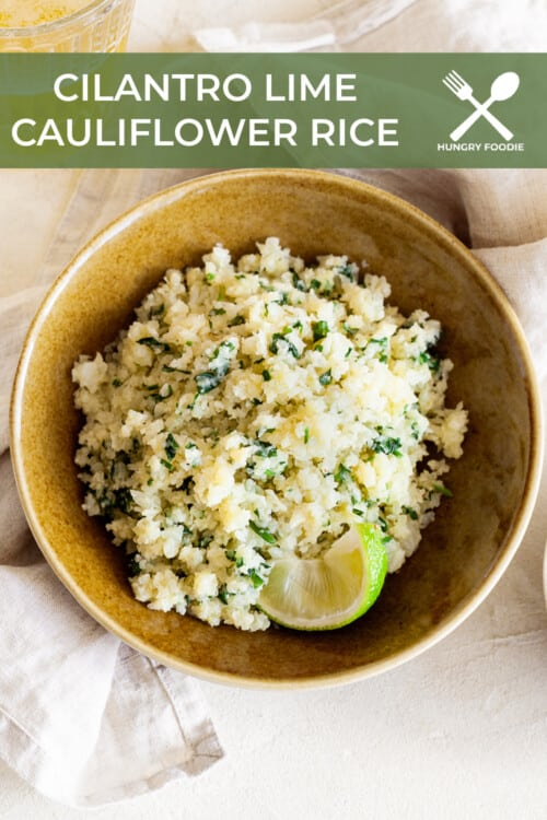 wooden bowl full of cilantro lime cauliflower rice, garnished with fresh lime wedges